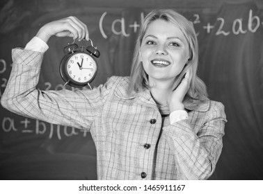 Girl school lecturer. Welcome teacher school year. Health and daily regime. Educator start lesson. She cares about discipline. Woman teacher hold alarm clock. What time is it. Lessons schedule.
