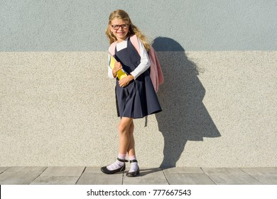 Girl in school uniform, with a backpack, glasses and notebooks. Background gray wall, Copy spsce