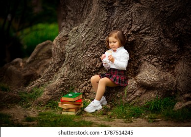 a girl in school uniform, eating a sandwich near a large tree, during a break between classes at school