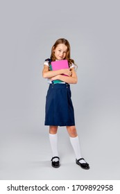 girl in school uniform holds school notebooks in hands