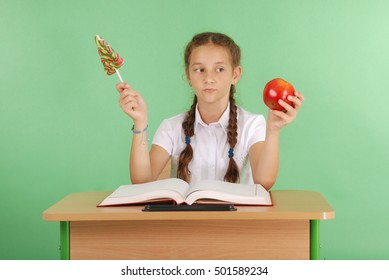 Girl in a school uniform sitting at the desk and choose candy or an apple isolated on green