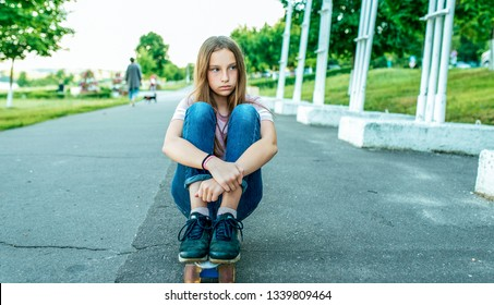 Girl schoolgirl 13-14 years old, sitting in the summer in the city on a skateboard, asphalt road. Sad tired, rest after riding a skateboard. Free space for text.
