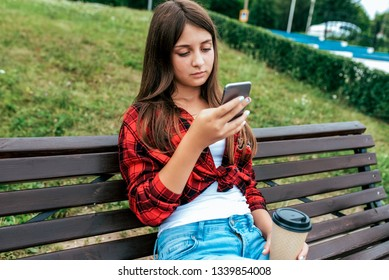Girl schoolgirl 14-15 years old sitting on a bench in his hand phone. Online chat application in social networks, prints and watches videos on your smartphone. A cup coffee tea in summer in city.