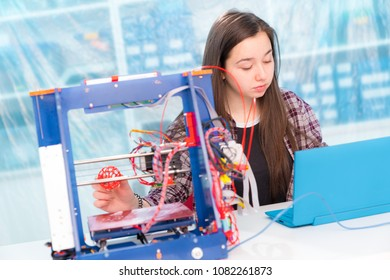 Girl schoolgirl with a 3D printer