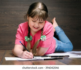 Girl schoolgirl draws lying on a wooden floor. The white paper, colored pencils. The girl has dark long hair