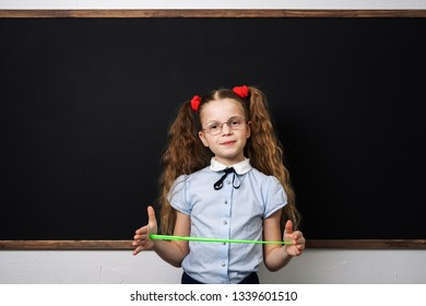 A girl schoolgirl is standing at the school board and holding a pointer.