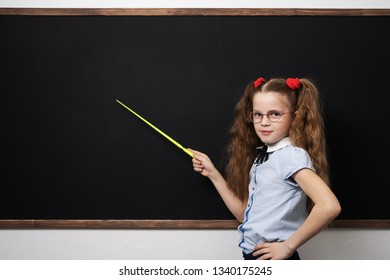 Girl schoolgirl is standing at the school board and shows a pointer to the board.