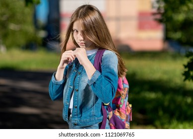 Girl schoolgirl. Summer in nature. It is in rack. I'm ready to start a fight. The concept of child protection, attack conflicts, resistance problems. Emotion of Courage And self-confidence.
