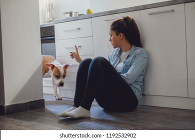 Girl scolding her dog while sitting on the kitchen floor