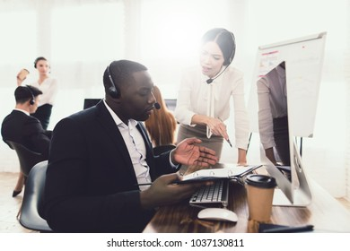 The girl scolds the man operator of the call center. They look at the computer screen. There was a mistake.
