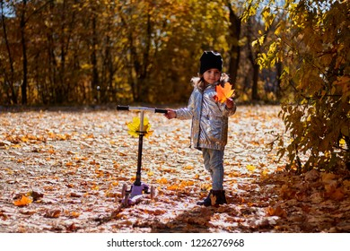 girl with scooter in autumn landscape