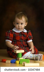 Girl in the scottish dress plays with the cubes