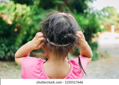 A girl scratch on her hair. The head lice makes itself at home on the kids hair.This annoying parasite can cause itching and other mild symptoms.