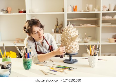 Girl sculptor in a workshop sculpts a clay kettle