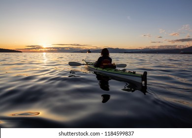Girl Sea Kayaking during a vibrant sunny summer sunset. Taken in Vancouver, BC, Canada.