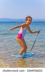 Girl in the sea learning to stand on the small surfboard