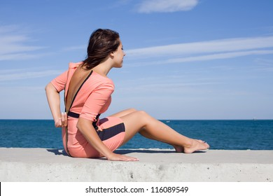 Girl at the sea. Girl unzips pink dress sitting on seashore