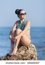 Girl at the sea. Young woman in sunglasses sitting on rocky seashore looking away
