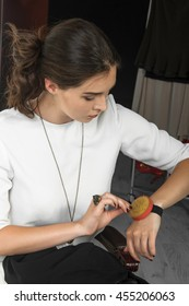 Girl seamstress working in the studio. She has a bracelet with needles on her arm. She has brown hair and is wearing a light blouse.