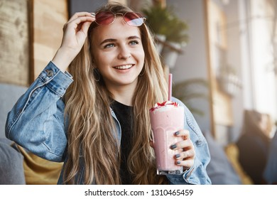 Girl seeing familiar face on street while sitting in local cafe outdoors, taking of sunglasses to take a look, holding cocktail, inviting friend to sit and talk with her while meeting unexpectedly