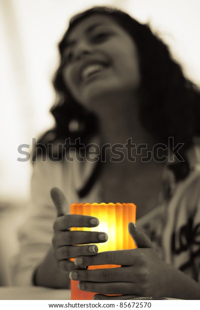 A girl seeking warmth from a lit candle.