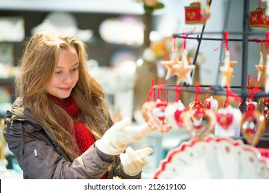 Girl selecting decoration on a traditional Christmas market