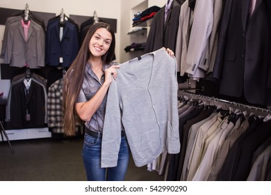 Girl seller offers the customer to try a cardigan in menswear boutique