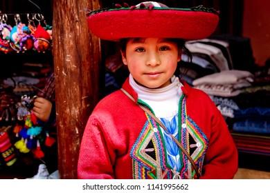 Girl selling handicrafts, Offers purses, dolls, and woolen fabrics, January 2018, Chincheros Cusco, Peru.