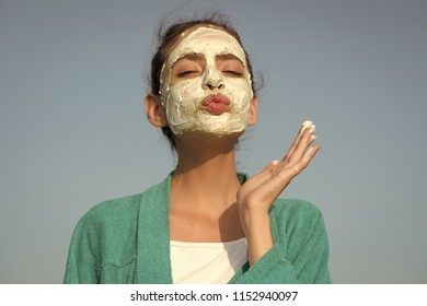 Girl send air kiss with cream mask on face on blue sky. Beauty, nature, youth, skin care, rejuvenation concept