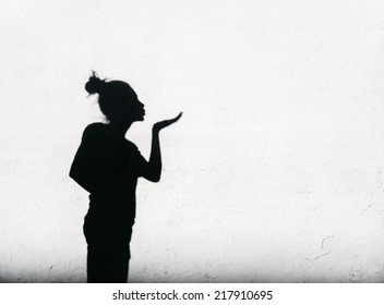 Girl sending air kiss around on white wall background. Shadows of woman