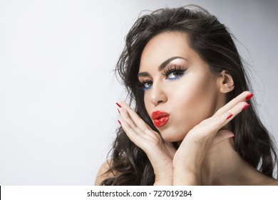 girl sending kiss with red lips, studio shot