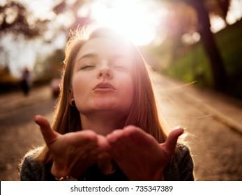 Girl sends an air kiss, sun, sunset