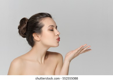 Girl sends a kiss closed her eyes. She has a clean well-groomed skin and long brown hair. Close-up portrait against a light gray background.