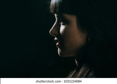 Girl with sensual face in dark room. Night, beauty, mystery, tender, gothic style, fashion concept. Woman with open mouth, full lips and luxury earrings. Female face with brown eyes and dark hair.