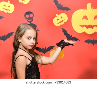 Girl with serious face on red background showing bats and pumpkins decor. Halloween party and decorations concept. Little witch with fair hair. Kid in black costume holds bat decoration