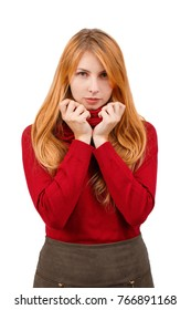 A girl with a serious look holding her hands over the neck of a sweater. Isolated.