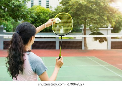 Girl serving on a badminton match on the outdoors court