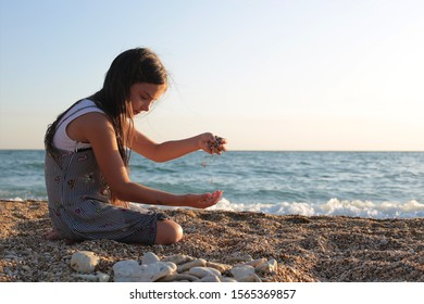 A girl of seven years old plays on the seashore pebbles
