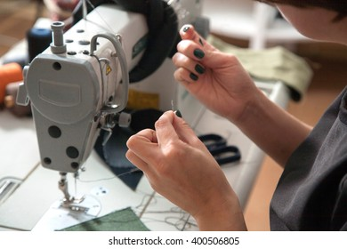 the girl is sewing on the sewing machine in the studio