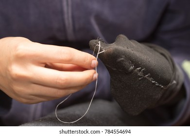 A girl sews a sock with a needle