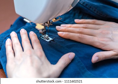 Girl sews a suit of blue cloth with the sewing machine.
