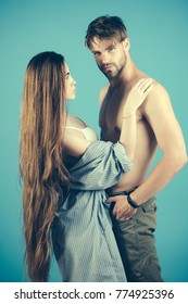 Girl in sexy bra touch man with bare torso on blue background. Couple in love. Erotic games, desire concept