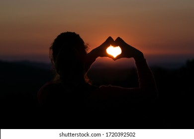 Girl shaping hearth symbol with hands at beautiful romantic sunset. Hands in hearth shape around the sun. Romantic sunset with loved one. Sunset on a mountain.