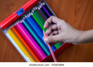 A girl sharpened her multi coloured pencil and getting ready for school