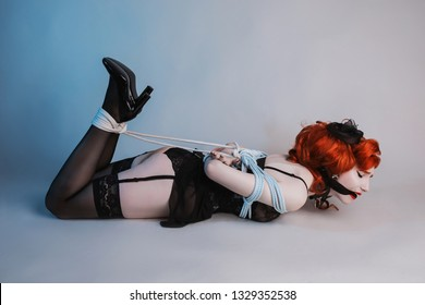 Girl in shibari rope. Sexual bdsm toy. Slave with tied legs and with gag in mouth. Bbdsm violence concept. Victim with rope bondage on legs. Shibari jute for bdsm. Violence in society. Gag bondage