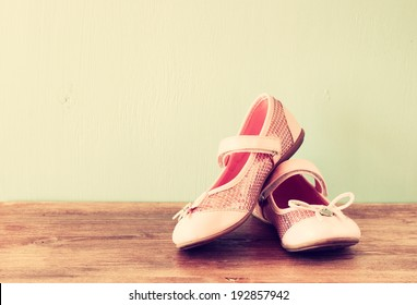 girl shoes over wooden deck floor. filtered image