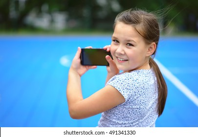 Girl is shooting photo using smartphone, outdoor shoot