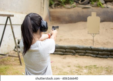 Girl shooting target with gun