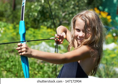 Girl shoots a bow on background of nature