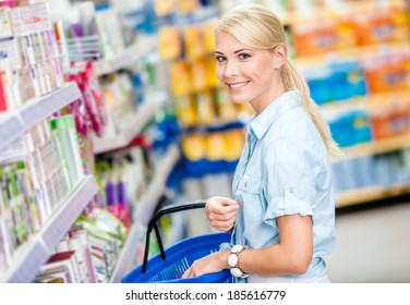 Girl at the shop choosing cosmetics among the great variety of products. Concept of consumerism, retail and purchase